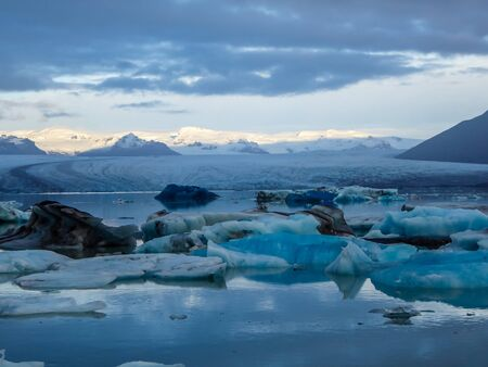 Beautiful glacier lagoon. Thousands of icebergs drifting lazily towards the sea, shining in many shades of blue. Soft sunset in the back. Thick clouds above the lagoon. Glacier's cap in the back Zdjęcie Seryjne