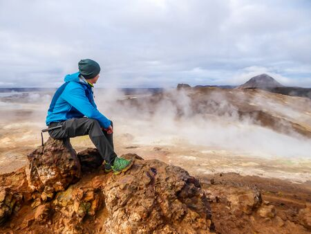 Young man wearing a blue jacket sits on top of a mud mountain, overlooking a geothermal spot noted for its bubbling pools of mud & steaming fumaroles emitting sulfuric gas. Power of planet Earth.