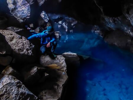 A young man wearing blue jacket squats at the rock in  Grjótagjá Cave, looking down at the crystal blue water. Famous Game of thrones location. The water in this cave is full of minerals, it's hot pot