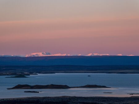 Sunrise over lava fields. Soft colors of the sky. High mountains in the back covered with snow. Lake in the middle, shines bright. Volcanic landscape, alienation and solitude. Harsh conditions. Zdjęcie Seryjne