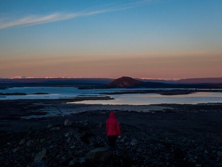 Girl wearing pink jacket walks around the top of the volcano. Sunrise on the horizon. Ground is covered with volcanic lava. In the back foam is coming out of the ground. Geothermal energy. Steam power