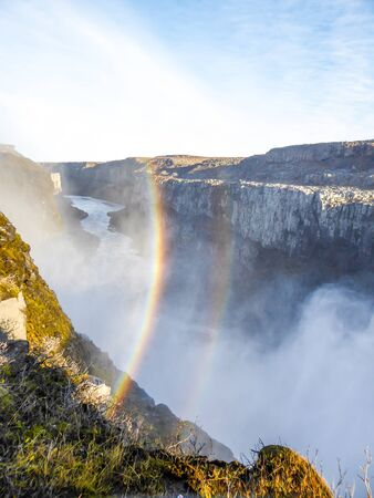 A beautiful rainbow over the waterfall gorge. The rainbow comes from the bottom of the gorge, where the water sprinkles. Stony and grassy shore of the gorge. Clear weather. Power of the nature.