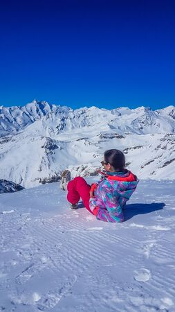 A girl in skiing outfit lies on the snow and enjoys the view on Alps in front of her. The sky is clear blue. Girl is looking front at the tall mountains. Slopes are perfectly graveled Zdjęcie Seryjne