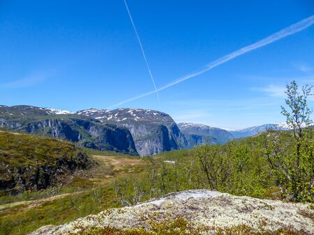 A view on higher parts of Eidfjorden, Norway. Taller mountains have some snow on them. Lush green flora growing on the slopes. Sky is clear blue, with traits of two plains crossing it.