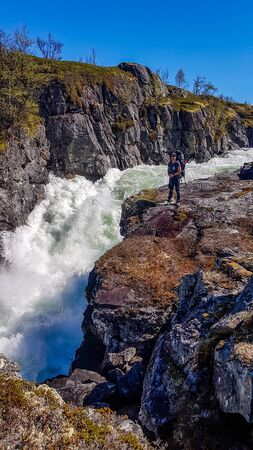 A man standing next to a rough river valursfossen in the highland village Vivelid, Norway. The rough river flown is a gorge. The water is very foamy. Powerful current, tall rocks are slippery and dangerous. Zdjęcie Seryjne