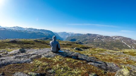 A young man wearing a hoodie sit at the ground and enjoys the endless mountain view of Eidfjord. He is relaxed. In the back taller mountains are covered partially with snow. Clear and sunny day.