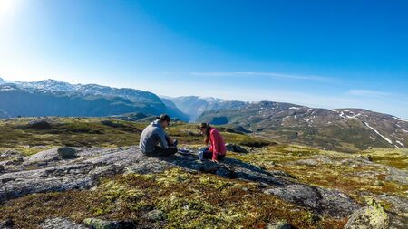 A couple having a picnic in the wilderness. Sausages and bread being grilled on a small transportable grill. In the back taller mountains are covered partially with snow. Clear and sunny day.