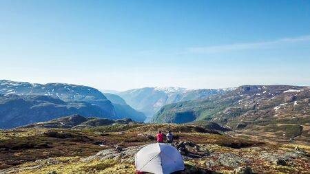A couple sitting at the rock, enjoying the view on Eidfjord, Norway. They are camping in the wilderness. There is a tent behind them. Adventurous couple, living life to the fullest. Freedom and relax Zdjęcie Seryjne