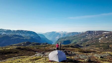 A couple standing at the rock, enjoying the view on Eidfjord, Norway. They are camping in the wilderness. There is a tent behind them. Adventurous couple, living life to the fullest. Freedom and relax