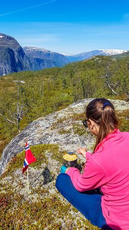 A girl sitting on a rock and cooking on a transportable little stove. Outdoor kitchen. She is cooking pasta in the wilderness. On the side a Norwegian flag waves slowly. In the back Eidfjorden