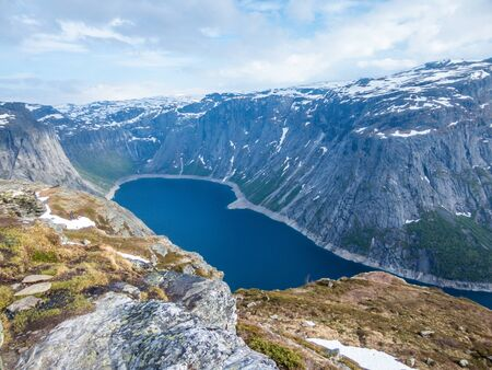 A beautiful view from the above on Ringedalsvatnet lake, Norway. Lake is located in between tall mountains. Slopes of the mountains are partially covered with snow. The water of the lake is navy blue.
