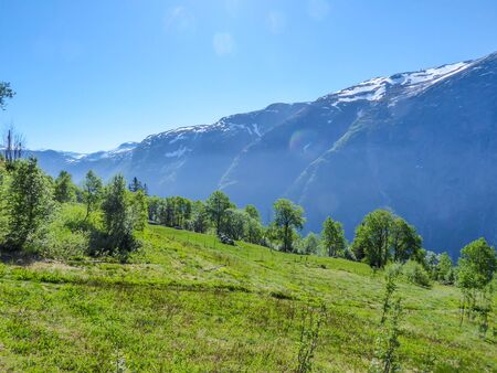 An majestic view on Eidfjord from Kjeasen, Norway. Slopes of the mountains are overgrown with lush green grass.  Taller parts of the mountains are barren. Sunny and clear day perfect for a hike.