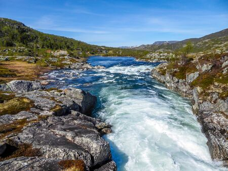 A wast river flowing in higher parts of Eidfjorden, Norway. Taller mountains have some snow on them. Lush green flora growing on the slopes. Sky is clear blue, with traits of two plains crossing it. Zdjęcie Seryjne