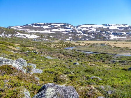 A wast meadow spreading through highlands of Hordaland county, Norway. Taller mountains are still partially covered with snow. River flowing in the bottom. Clear and sunny day, perfect for a hike.