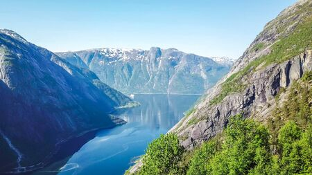 An majestic view on Eidfjord from Kjeasen, Norway. Slopes of the mountains are overgrown with lush green grass. Water has dark blue color. Taller parts of the mountains are barren. Sunny and clear day