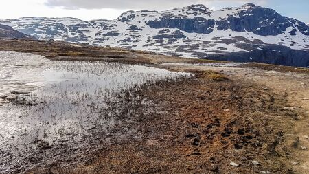 A paddle, deriving from the melting snow spreading on a barren meadow. Taller mountains in the back covered with snow. Nature wakes up after long winter vegetation. Zdjęcie Seryjne