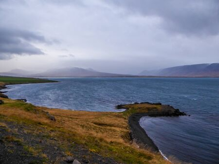 Grassy coast of the fjord with tall mountains in the back. The grass has green shades. Water of the fjord is calm. Great overcast. A headland covered with lava stones. Taller mountains in the back