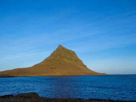 A stunning view on famous Iceland's mountain, Kirkjufell. In front of the tall hat-like mountain spreads the shallow water of a fjord. Beautiful and clear day, popular destination for a holiday.