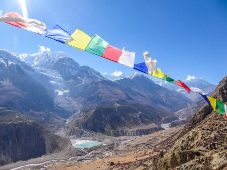 """Waving flags with mantra """"Om mani padme hum"""" on them. Wind blows them over Himalayan peaks. Very weary flags. High peaks covered with snow. meditation and retreat"""