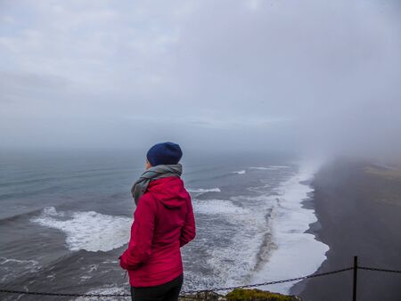 A girl wearing a pink jacket and a beanie standing at the top of the cliff with her hands in the pockets, looking at the rough sea below. Waves wash the black sand beach abruptly. Moody and mysterious
