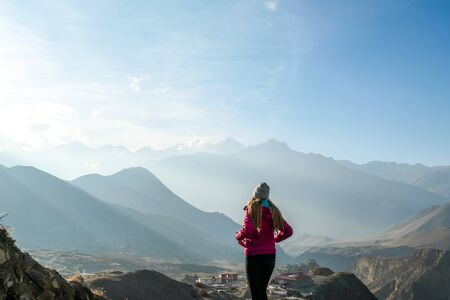 A girl wearing pink jacket standing on a top of a mountain and enjoying the misty Himalaya range spreading in front of her. The sun light is nicely marked. Freedom and achievement.