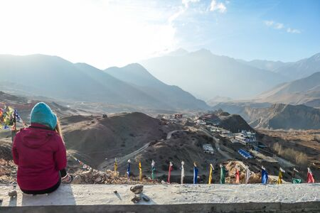 A girl wearing pink jacket sitting on a concrete wall on a top of a mountain and enjoying the misty Himalaya range spreading in front of her. The sun light is nicely marked. Freedom and achievement.