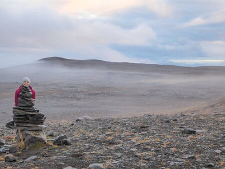 A girl wearing pink jacket and a beanie hiding behind a stone man. Only her head is popping out, pretending to be the head of the stone man. Vast stony landscape around, covered with mist. Having fun