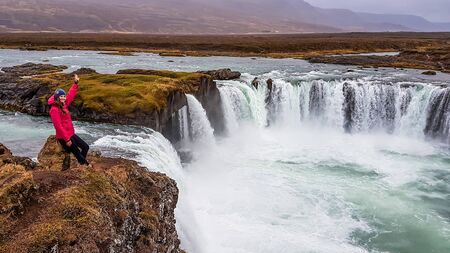 A girl wearing pink jacket stands at the top of a massive Godafoss waterfall. She spreads her arms wide, having fun and being happy. The waterfall consist of few separated smaller falls. Rainy day