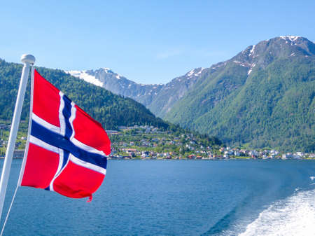 Norwegian flag hanging on  the railing of the ship and waving above the water.The motor of the ship makes the water wavy and foamy. Tall, lush green mountains surrounding the fjord. Clear blue sky. Stockfoto