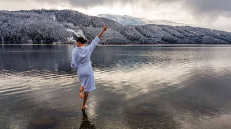 Girl in a white bathrobe walking in a shallow water of a lake. Girl is holding one hand up, gesture of happiness. On the other side of the lake there are mountains covered with snow Winter alpine spa