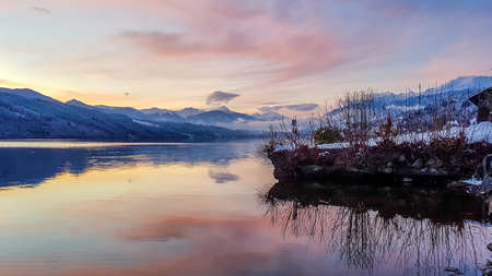 Beautiful view on Millstätter lake in Austria. The lake is surrounded by Alps. Mountains are covered with snow. The sky is exploding with pink and orange. Stunning sunset. Shore overgrown with bushes
