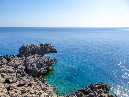 A blue lagoon in Cape Greco, Cyprus.  The water has many shades of blue. Crystal clear water. Sharp rocks emerging from the sea. Calm surface of the sea. Bright and sunny day.