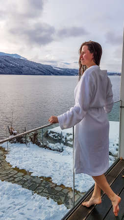 A girl in a white bathrobe standing on the balcony of a SPA in Austria in winter. She has wet hair. She is enjoying the view on Millstätter lake and mountains in front of her. She is feeling relaxed