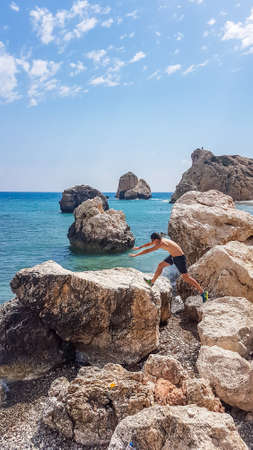 A young man jumping between sharp rocks in Aphrodite's Birthplace, Petra tou Romiou, Cyprus. Sea is calm, in turquoise shade. Other smaller boulders emerging from the sea. Freedom and relaxation