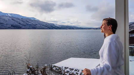 A girl in a white bathrobe standing on the balcony of a SPA in Austria in winter. She has wet hair. She is enjoying the view on Millstätter lake and mountains in front of her. She is feeling relaxed Standard-Bild