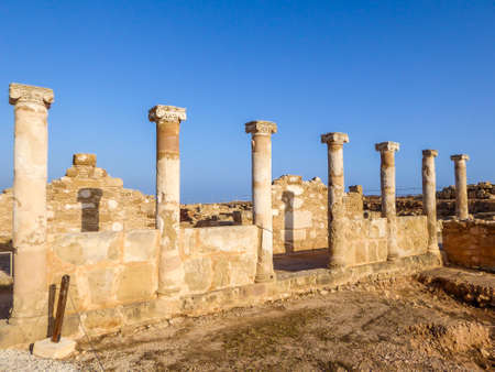 Ruins of an ancient temple, what is left are temple columns, Kato Paphos Archeological Park. Sandy color of the construction. Clear and blue sky.