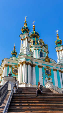 A young woman wearing black, sitting on the stairs in front of St Andrew's Church, Kiev, Ukraine. The church is relatively small and painted blue. Clear sky. Solo traveling girl.