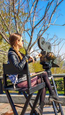 A girl in a leather jacket sitting at the director chair and pretending to be filming the surroundings. Girl looks very relaxed and chilled. She is having a great time while solo traveling.