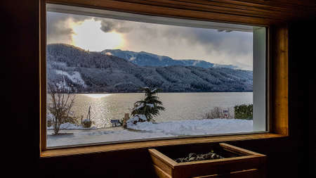 Alpine sauna with the view on the lake and the mountains. Under the window there is a furnace, warming the stones. Mountains covered with snow. Relaxation and chill in winter wonderland.
