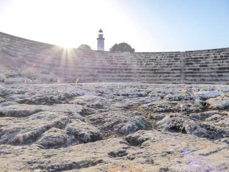 A view on amfiteater in Kato Paphos Archaeological Park, ancient Greek and Roman city in Cyprus. Sun is shining bright. In the back a lighthouse is visible. 写真素材