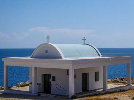 A little church located by the sea in Cape Greco, Cyprus. Church is white with a turquoise rooftop. Blue sea spreads in behind it. Barren slopes of the cliff. Endless horizon line.