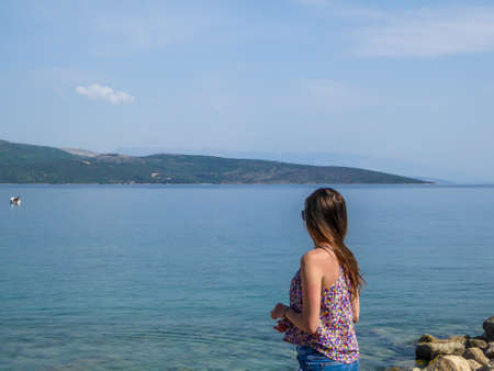 Girl with long hair stands at the shore of the Mediterranean Sea and looks at the calm surface of the water. She is calms and peaceful. Water has many shades of blue. In the back there are islands