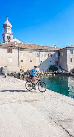 A man in blue tank top and a full cap standing on her bike and admiring the view on the Mediterranean Sea. Behind him there is an old city center of Krk. Active traveling. Clear and sunny weather.v