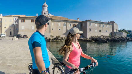 A couple in full caps standing on their bikes, taking a selfie and admiring the view on the Mediterranean Sea. Behind them there is an old city center of Krk. Active traveling. Clear and sunny weather