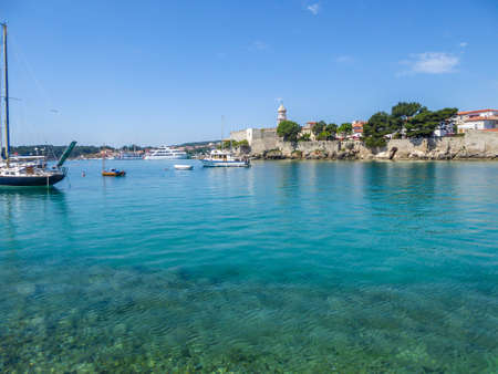 Sea view on Croatian city Krk. The city is build directly by the sea. Thick walls emerge high up from the sea line, defence building. There is a church tower, towering above other constructions.