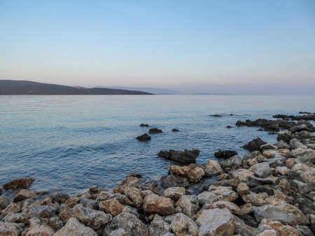 Stony beach in Krk, Croatia. The Mediterranean Sea has a turquoise color. Surface of the sea is calm, there are no waves. In the back there are some mountains. Soft colors of the sunset.
