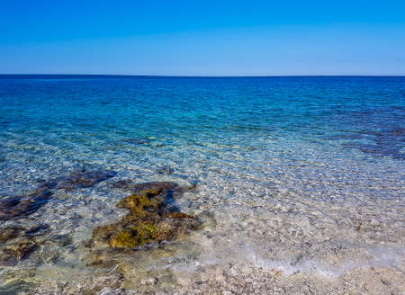 Calm, shallow sea water. There are barely any waves on the surface. The water is very clear, one can see the stony bottom. Few bigger stones protrude from water.