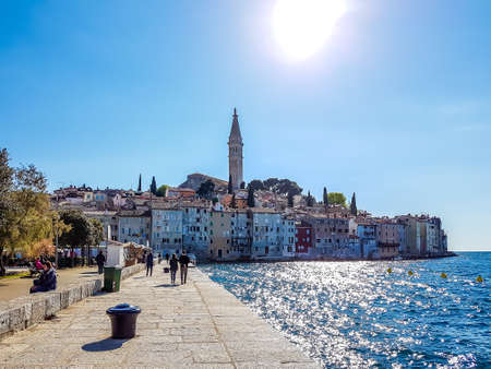 A view on city center of Rovinj, Croatia from the harbor promenade. Sun is reflecting in the calm sea water. Bright and sunny day. City located directly by the sea, on a little hill. Tall church tower Reklamní fotografie