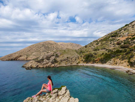Girl sitting on a rock with the view on Stara Baska Beach. Girl is enjoying the beautiful view, being very happy. Sea in the bay is very calm, shimmering with many shades of blue. Croatian hidden gem