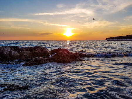 Romantic sunset by a stony seashore. The sun sets over the horizon. The sun beams reflecting in the calm sea waters. Stony shore is washed by the gentle waves. The sky is turning yellow and orange.